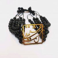 این دستبند زنانه با پلاک جمله استیل طلایی ( من مست می عشقم ) و مروارید