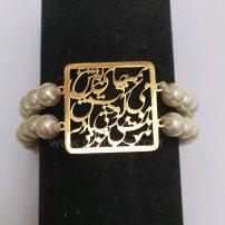 این دستبند زنانه با پلاک جمله استیل طلایی ( همه جا بوی عشق می پیچد وقتی باد به موهات خورد ) و مروارید